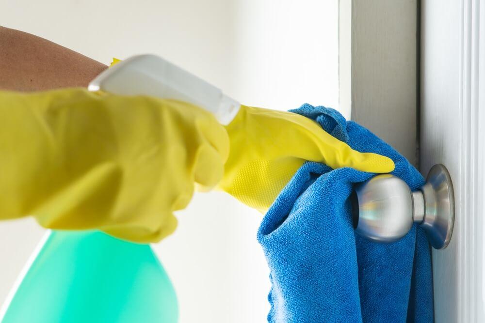 hand cleaning doorknob